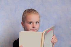 Mädchen mit dem blonden Haar ein Buch lesend Stockbild