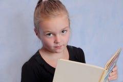 Mädchen mit dem blonden Haar ein Buch lesend Lizenzfreie Stockfotografie