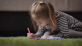 Mädchen mit dem blonden Haar, gekleidet in einem grauen gestreiften Kleid und in den Strumpfhosen sitzt auf dem grünen Teppich un stock footage