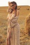 Mädchen mit dem blonden Haar im eleganten Kleid, das auf dem Heu aufwirft Stockbilder