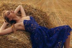 Mädchen mit dem blonden Haar im eleganten Kleid, das auf dem Heu aufwirft Lizenzfreie Stockbilder