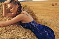 Mädchen mit dem blonden Haar im eleganten Kleid, das auf dem Heu aufwirft Lizenzfreie Stockfotografie