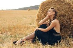Mädchen mit dem blonden Haar im eleganten Kleid, das auf dem Heu aufwirft Lizenzfreie Stockfotos