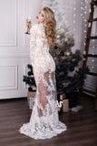 Mädchen mit dem blonden Haar trägt das luxuriöse Kleid und wirft neben Weihnachtsbaum auf Stockfoto