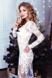 Mädchen mit dem blonden Haar trägt das luxuriöse Kleid und wirft neben Weihnachtsbaum auf Lizenzfreie Stockbilder