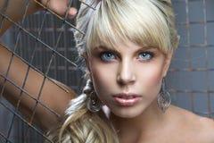 Mädchen mit dem blonden Haar und den großen Ohrringen Stockfotografie