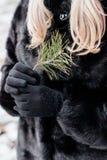 M?dchen mit dem blonden Haar und schwarzem Mantel stockbild