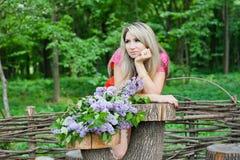 Mädchen mit dem Blumenstrauß der Flieder Lizenzfreie Stockfotos