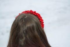 Mädchen mit dem braunen Haar in einem roten Band auf einem weißen Hintergrund Stockbild