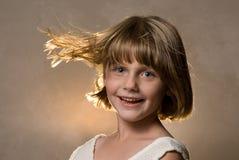 Mädchen mit dem durchbrennenhaar des Winds backlit Stockbild