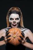 Mädchen mit dem erschrockenen skeleton Make-up, das Kürbis und das Schreien hält stockfotografie