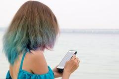 Mädchen mit dem farbigen Haar, das den Smartphone untersucht lizenzfreie stockfotos