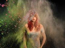 Mädchen mit dem farbigen Pulver, das um sie explodiert lizenzfreie stockfotos