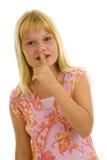 Mädchen mit dem Finger auf ihren Lippen Stockfoto