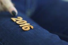 Mädchen mit dem Finger, der helle hölzerne Darstellungsnummer 2016 auf dem Hintergrund der Jeans zeigt Lizenzfreie Stockfotografie