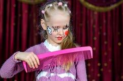 Mädchen mit dem Gesicht gemalten bürstenden Haar mit großem Kamm Stockbild