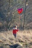 Mädchen mit dem Herz-förmigen Ballon, der auf einem Gebiet steht stockfotografie