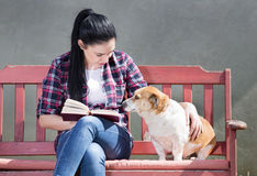 Mädchen mit dem Hund, der ein Buch liest Stockfotografie