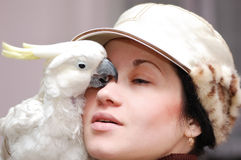 Mädchen mit dem Küssen des Papageien lizenzfreie stockfotografie