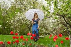 Mädchen mit dem Kleid, das Parkblume mit Regenschirm aufwirft Lizenzfreies Stockfoto
