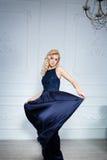 Mädchen mit dem langen blonden Haar im dunkelblauen Kleid Lizenzfreie Stockbilder