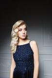 Mädchen mit dem langen blonden Haar im dunkelblauen Kleid Lizenzfreie Stockfotos