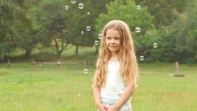 Mädchen mit dem langen gelockten Haar, das Seifenblasen im Garten auf einem Hintergrund von Bäumen betrachtet Langsame Bewegung stock video footage