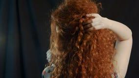 Mädchen mit dem langen gelockten roten Haar auf einem Schwarzen stock video footage
