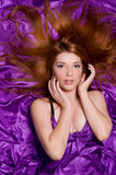Mädchen mit dem langen Haar auf purpurrotem Gewebe lizenzfreies stockbild