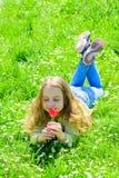 Mädchen mit dem langen Haar, das auf grassplot, Grashintergrund liegt Kind genießen Duft der Tulpe beim Lügen an der Wiese Mädche lizenzfreies stockbild