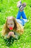 Mädchen mit dem langen Haar, das auf grassplot, Grashintergrund liegt Kind genießen Duft der Tulpe beim Lügen an der Wiese Frühli lizenzfreie stockbilder