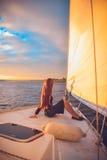 Mädchen mit dem langen Haar, das am Heck der Yacht und der Blicke in den Abstand bei Sonnenuntergang sitzt Stockbild