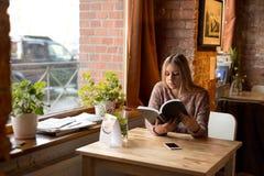 Mädchen mit dem langen Haar, das am Tisch sitzt und Zeitschrift schaut Lizenzfreies Stockbild