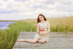 Mädchen mit dem langen Haar im Wasser im Sommer mit Erdbeeren Stockfotografie