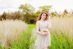 Mädchen mit dem langen Haar im Wasser im Sommer mit Erdbeeren Stockbild