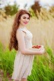 Mädchen mit dem langen Haar im Wasser im Sommer mit Erdbeeren Lizenzfreie Stockfotografie