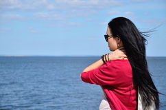 Mädchen mit dem langen Haar, welches das Meer betrachtet Stockfotografie