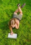 Mädchen mit dem Laptop, der auf Rasen liegt Stockfoto