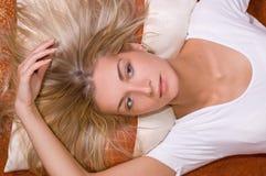 Mädchen mit dem natürlichen blonden Haar, das auf dem Fußboden liying ist Lizenzfreies Stockfoto