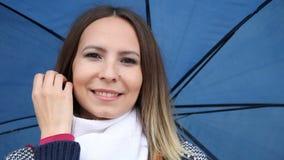 Mädchen mit dem Regenschirm, der Haar verbessert und Blinzeln im Freien stock video footage