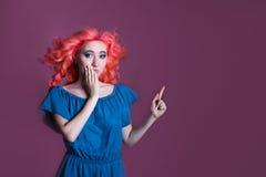 Mädchen mit dem rosa Haar im blauen Kleid zeigt Zeichen auf lila Hintergrund, Platz für Text Stockfotografie