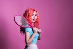 Mädchen mit dem rosa Haar spielt Tennis auf einem rosa Hintergrund Stockfoto