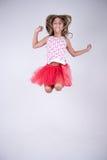 Mädchen mit dem rotem Rockspringen glücklich und dem Lächeln mit den Händen dem oben und Haar im Wind Stockfoto