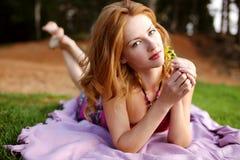Mädchen mit dem roten Haar auf grünem Gras Stockfoto