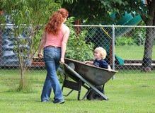 Mädchen mit dem roten Haar, das blondes Kleinkind in Wheelb drückt Lizenzfreie Stockfotografie