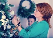 Mädchen mit dem roten Haar in einem grünen Kleid kleiden oben den Weihnachtsbaum Stockfotos
