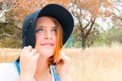Mädchen mit dem roten Haar, Overall und schwarzem Hut, die auf dem Gebiet stehen Lizenzfreie Stockfotografie