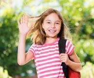 Mädchen mit dem Rucksack, der draußen aufwirft Lizenzfreie Stockfotos