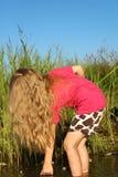 Mädchen mit dem schönen langen goldenen Haar auf dem Ufer des Sees Lizenzfreie Stockfotos