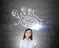Mädchen mit dem schwarzen Haar und Gehirn mit Glühlampen Lizenzfreie Stockfotografie
